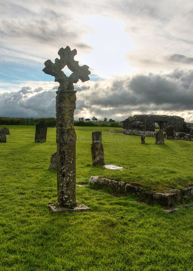 Vecchio incrocio di pietra celtico sul cimitero in pieno di erba verde immagini stock libere da diritti