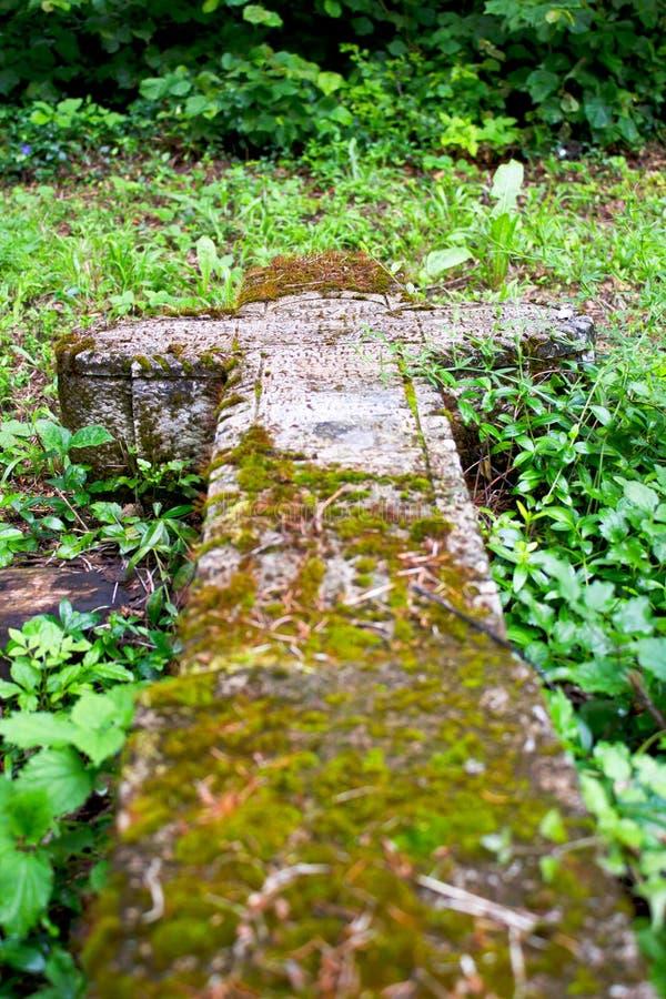 Vecchio incrocio di pietra cristiano sull'erba immagini stock libere da diritti