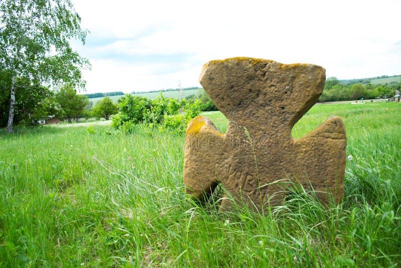 Vecchio incrocio di pietra su un prato verde fotografie stock