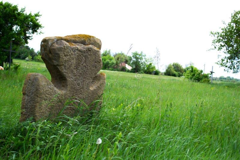 Vecchio incrocio di pietra su un prato verde immagine stock libera da diritti