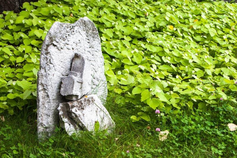 Vecchio incrocio di pietra su un prato verde fotografie stock libere da diritti