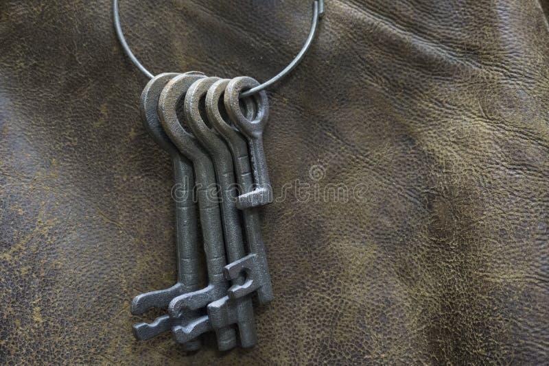 Vecchio insieme delle chiavi con un fondo di cuoio immagini stock libere da diritti