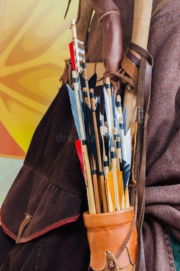 Vecchio insieme delle frecce di legno storiche con piume luminose in un fremito di cuoio, fondo immagine stock libera da diritti