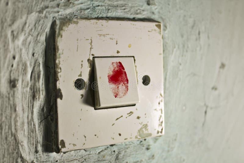 Vecchio interruttore della luce sulla vecchia parete verde con l'impronta digitale sanguinosa su  immagine stock