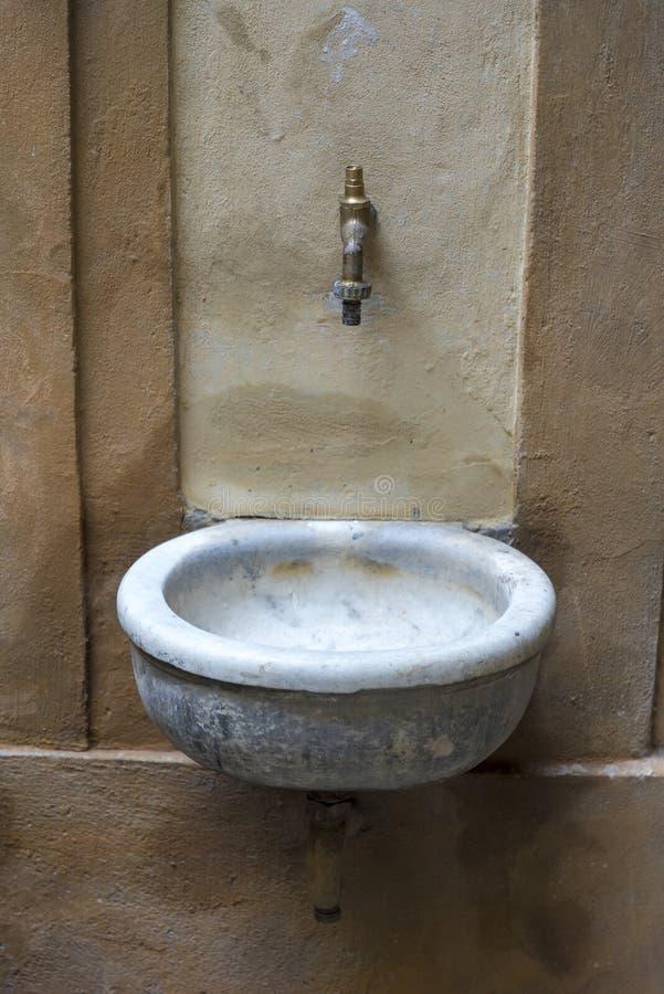 Vecchio lavabo sulla parete della casa, arrugginita e non funzionante immagine stock