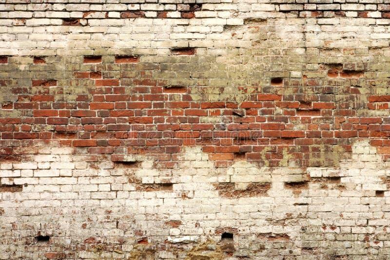 Vecchio lavoro di muratura rotto dai mattoni bianchi rossi e dal gesso nocivo immagini stock