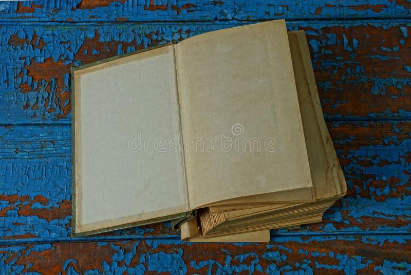 Vecchio libro aperto con le pagine marroni grige che si trovano su una tavola di legno blu e misera fotografia stock