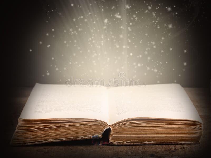Vecchio libro aperto con luce e le stelle cadenti magiche fotografie stock libere da diritti