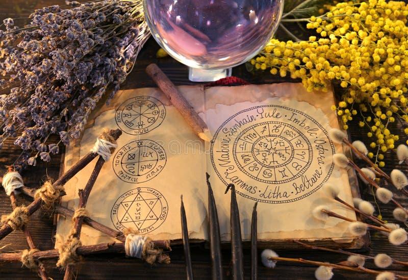 Vecchio libro con il grafico, il pentagramma, la sfera di cristallo e le erbe wiccan di feste fotografie stock