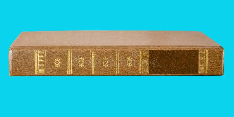 Vecchio libro con la spina dorsale su fondo blu, vista laterale, per progettazione fotografia stock libera da diritti