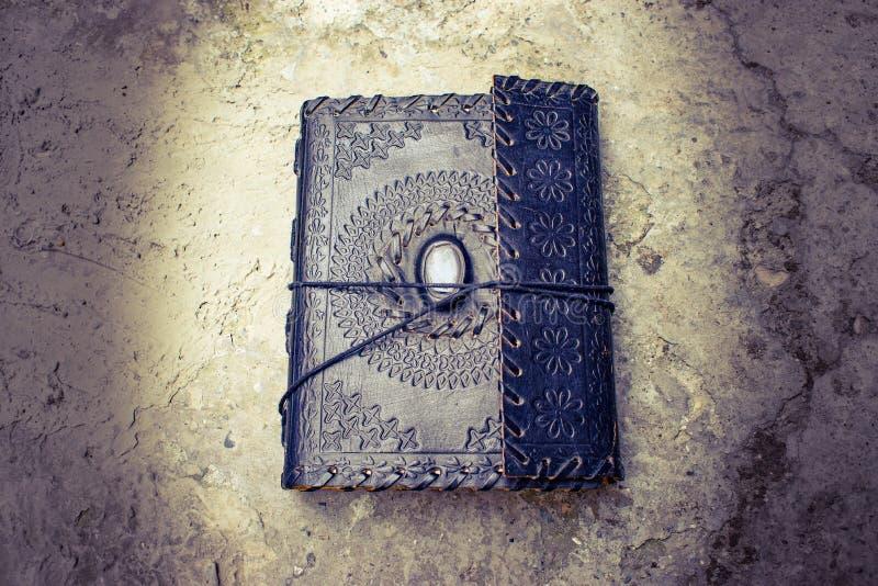 Vecchio libro rilegato di cuoio antico che si trova sulla terra immagini stock libere da diritti