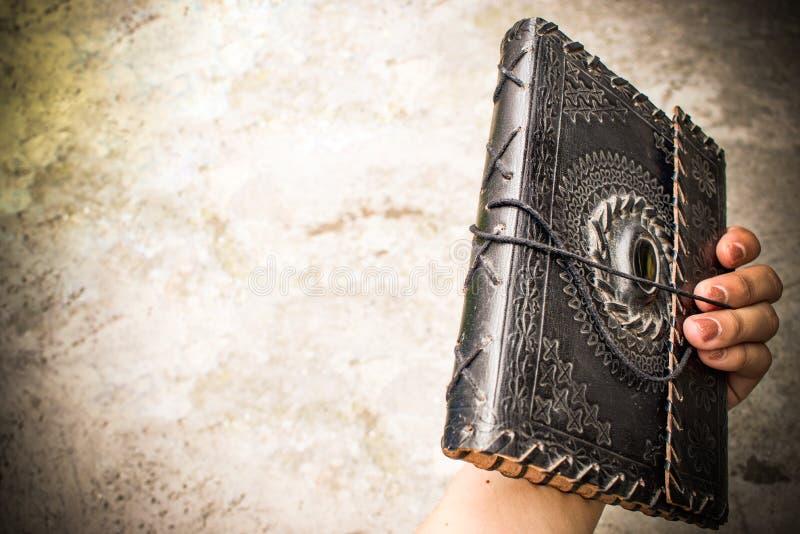 Vecchio libro rilegato di cuoio antico nell'OS della mano una donna immagini stock