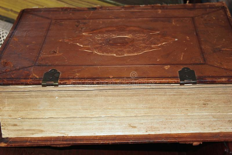 Vecchio libro rilegato di cuoio che si trova dal suo lato fotografia stock libera da diritti