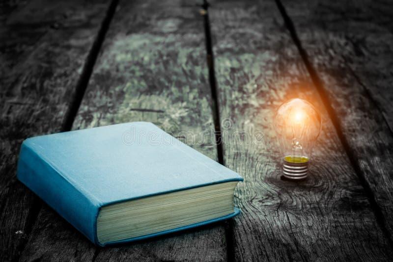 Vecchio libro stracciato su una tavola di legno Leggendo dal lume di candela Composizione d'annata Libreria antica Letteratura an fotografie stock