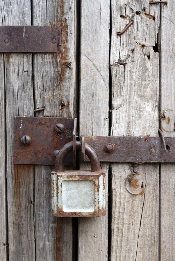 Vecchio lucchetto arrugginito sul portello di legno immagine stock
