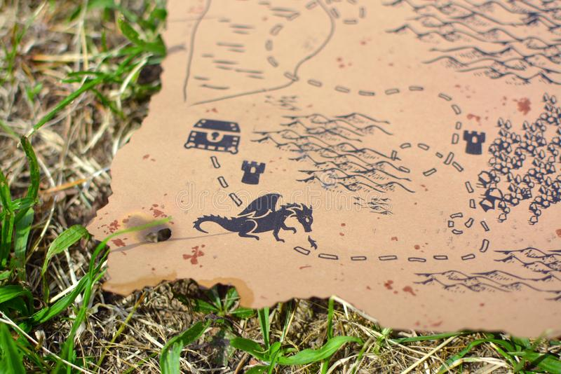 Vecchio mappa del tesoro bruciata del worlde stile antico con il petto garding del drago che si trova nell'erba fotografia stock