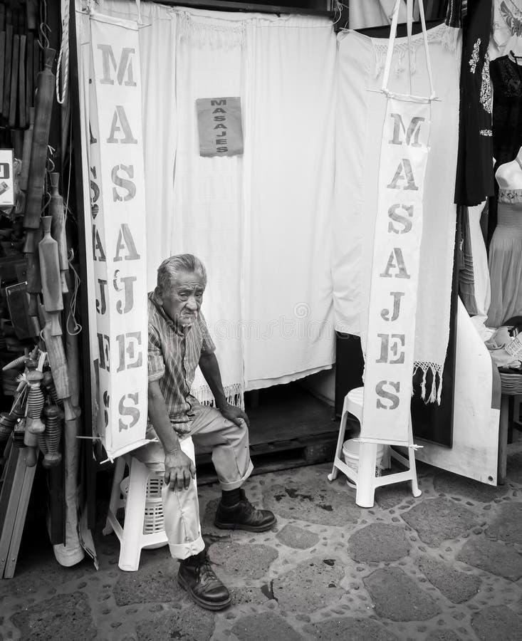 Vecchio massaggiatore che si siede fuori del suo salone di massaggio, immagini stock