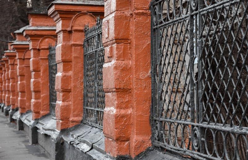 Vecchio mattone rosso e recinto nero della grata immagini stock
