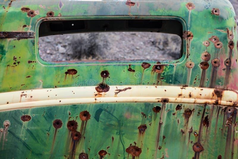 Vecchio metallo arrugginito dell'automobile con i fori di pallottola fotografia stock