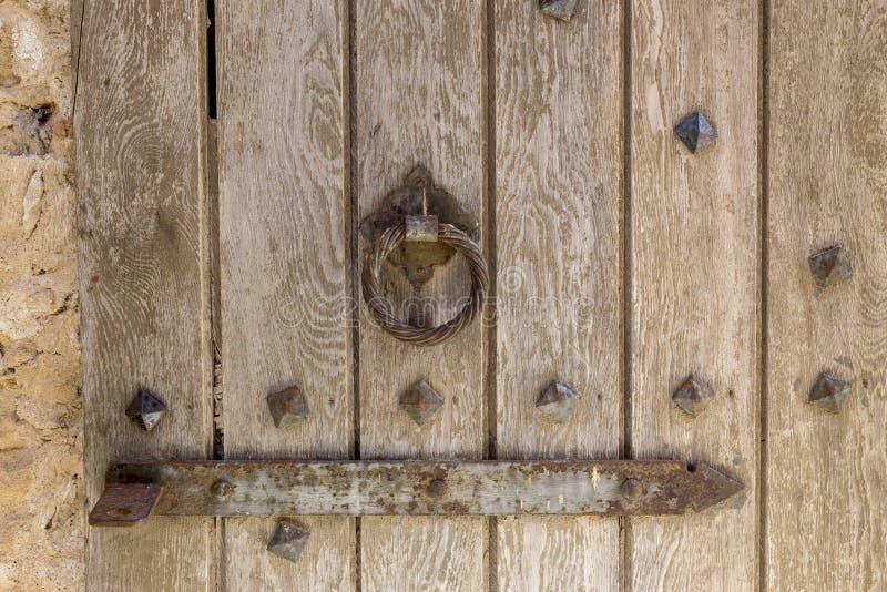 Vecchio, metallo, battitore della maniglia di porta sotto forma di anello su fondo di legno fotografia stock