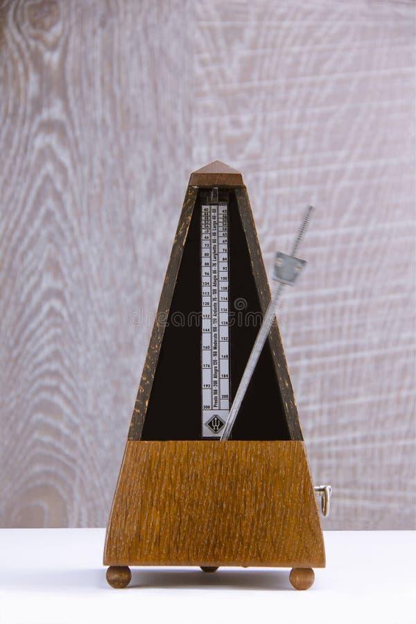 Vecchio metronomo in legno marrone nel moto su fondo di legno grigio immagine stock