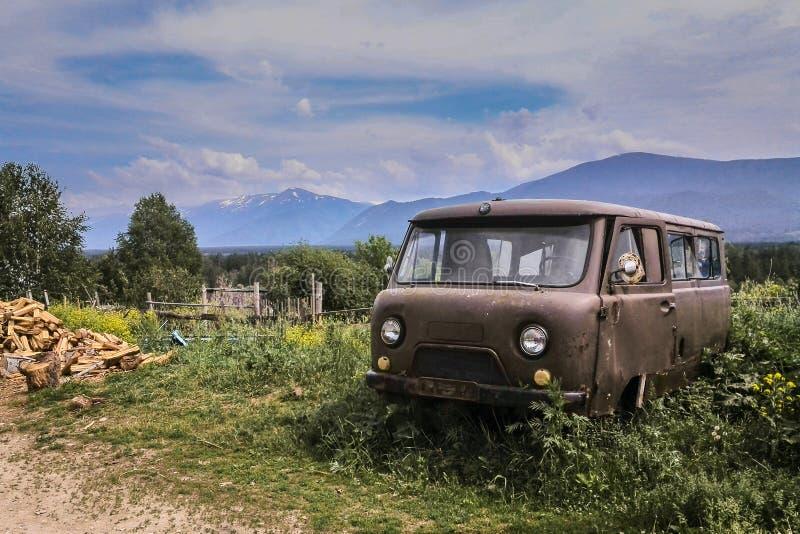 Vecchio minibus abbandonato arrugginito nel paesino di montagna, mucchio di legna da ardere, il Kazakistan orientale immagini stock libere da diritti