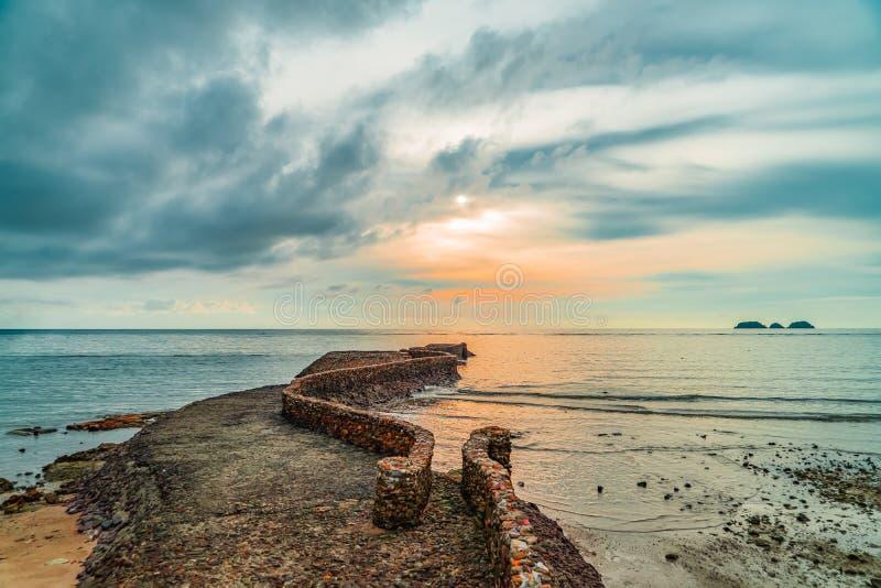 Vecchio molo della roccia del birck vicino alla linea costiera al tramonto fotografia stock