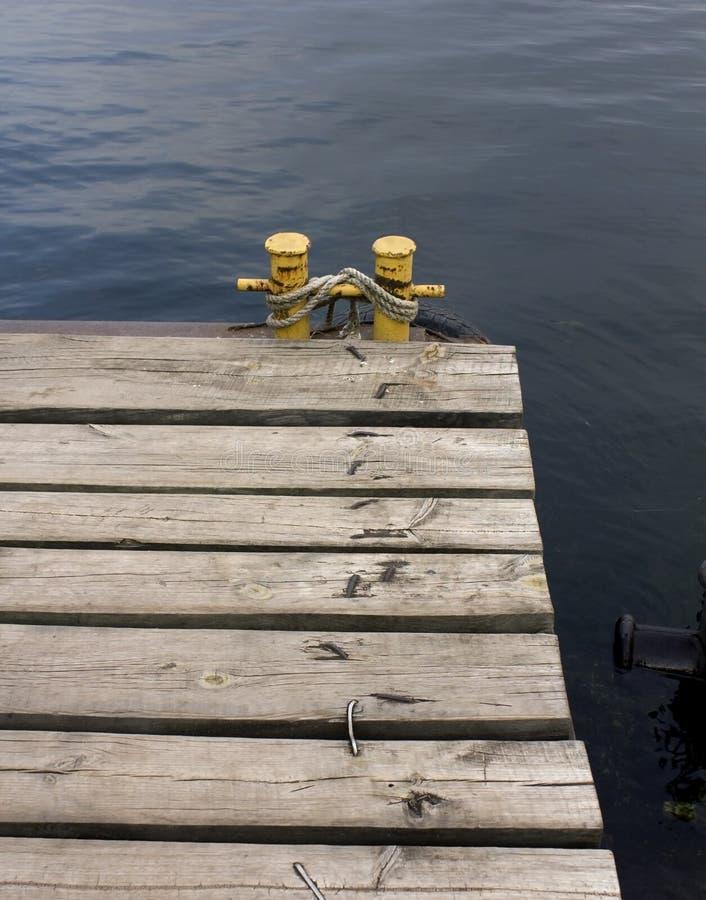 Vecchio molo di legno, bitta gialla con la corda fotografia stock