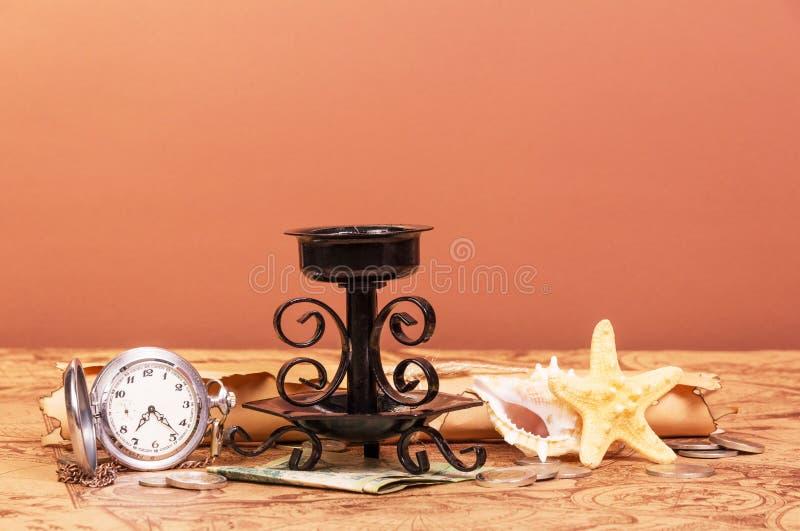 Vecchio mondo della mappa, pergamena, orologi, soldi, candeliere su rosso--orandevy fotografia stock