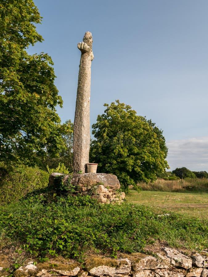 Vecchio monumento fatto della condizione di pietra su un prato immagini stock