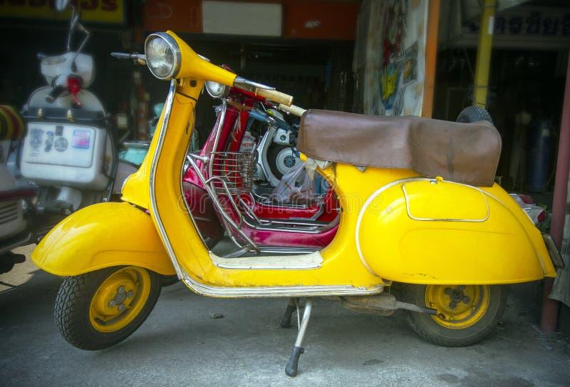 Vecchio motorino giallo nel negozio fotografia stock