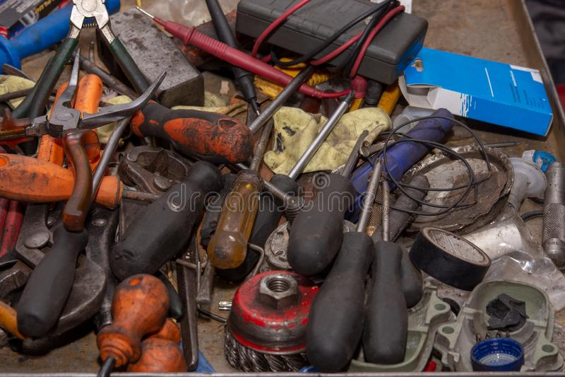 Vecchio mucchio arrugginito e sporco degli strumenti nell'officina del meccanico Automobile che ripara concetto con i vecchi stru immagini stock
