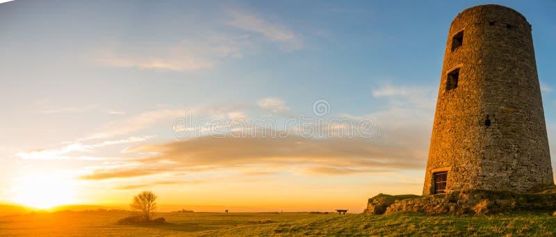 Vecchio mulino a vento al tramonto immagine stock