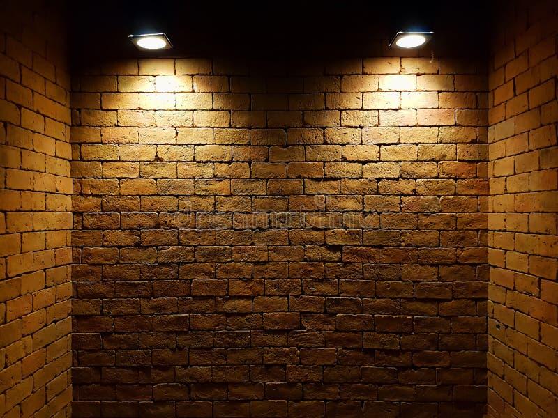Vecchio muro di mattoni astratto nello scuro con il riflettore due, tono leggero caldo muro di mattoni nella stanza vuota Priorit fotografie stock