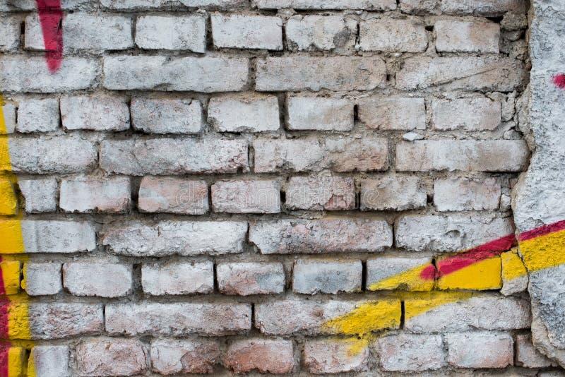 Vecchio muro di mattoni bianco dipinto con i dettagli gialli e rossi dei graffiti Priorità bassa bianca immagine stock