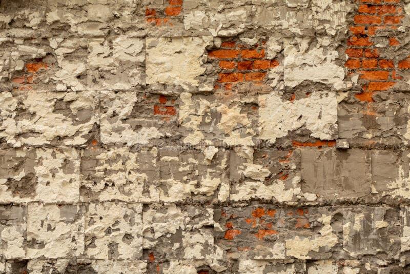 Vecchio muro di mattoni con gesso e calcestruzzo distrutti Smantellamento della costruzione fotografia stock