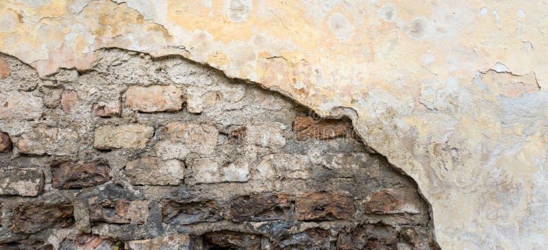 Vecchio muro di mattoni con struttura dello stucco della buccia Retro fondo indossato d'annata della parete Superficie astratta a immagine stock