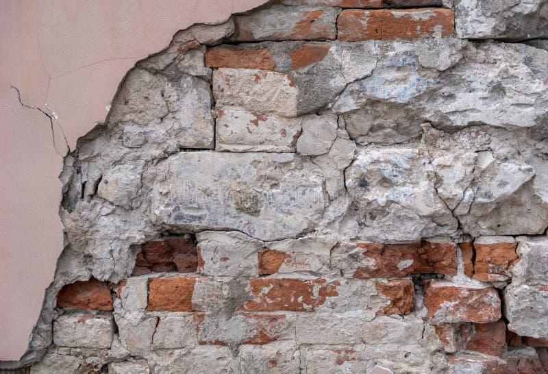 Vecchio muro di mattoni dilapidato, gesso di sbriciolatura immagine stock