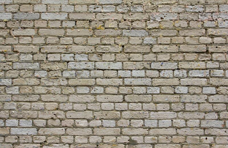 Vecchio muro di mattoni grigio avariato con cemento ed i fori scuri in mattoni Struttura della superficie ruvida fotografie stock libere da diritti