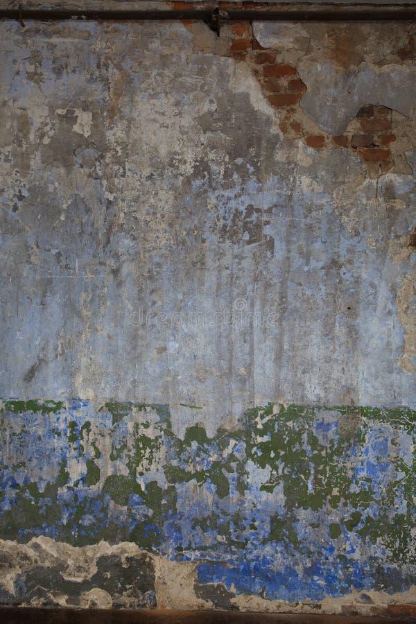 Vecchio muro di mattoni intonacato con i resti degli strati e dei colori differenti della pittura della sbucciatura immagine stock