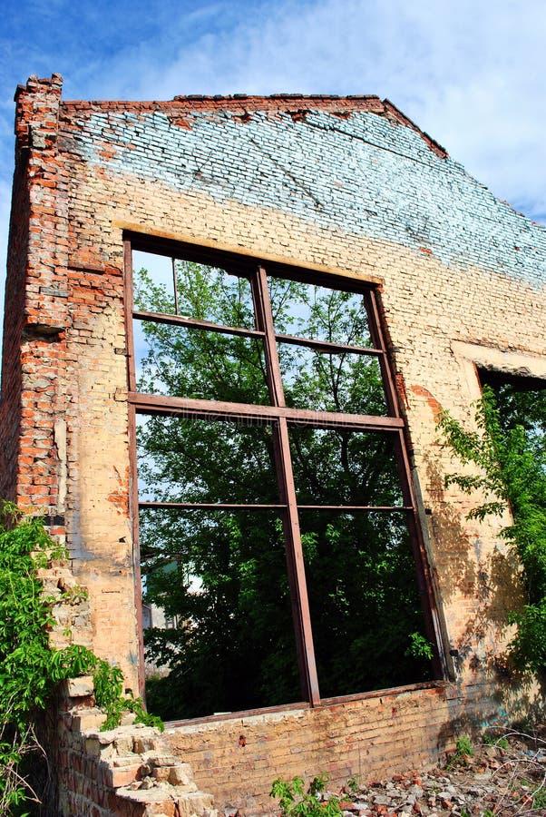 Vecchio muro di mattoni di sbriciolatura con la finestra senza vetro, alberi verdi e cielo della molla immagini stock