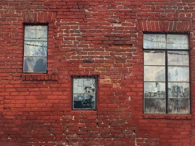 Vecchio muro di mattoni stesso necessitante indicare riparazione con tre finestre differenti, fondo architettonico fotografia stock libera da diritti