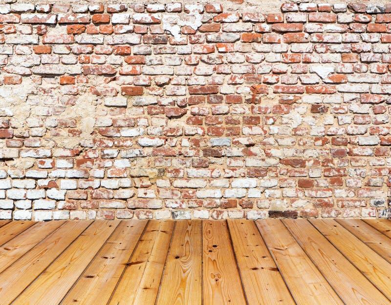 Vecchio muro di mattoni sul pavimento di legno immagine stock
