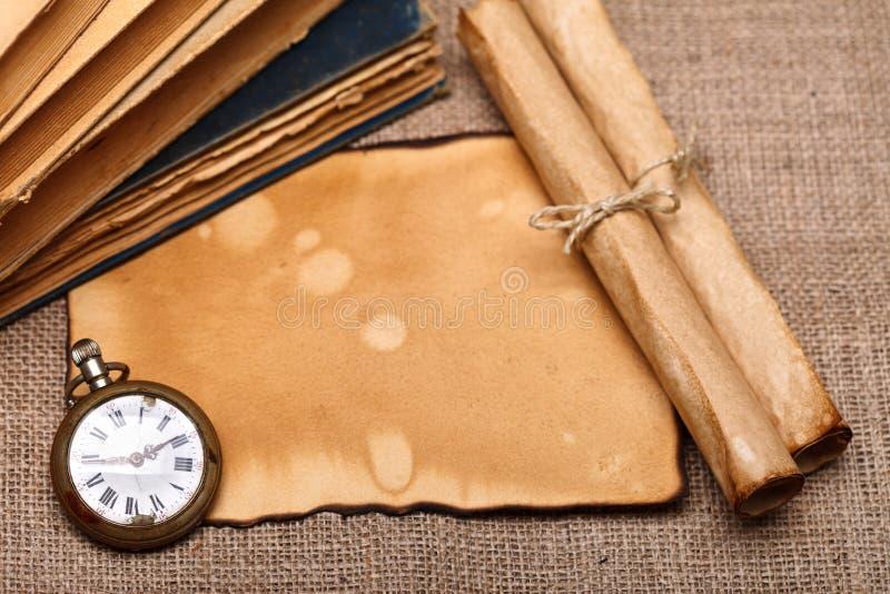 Vecchio orologio da tasca con i rotoli ed i libri immagini stock libere da diritti