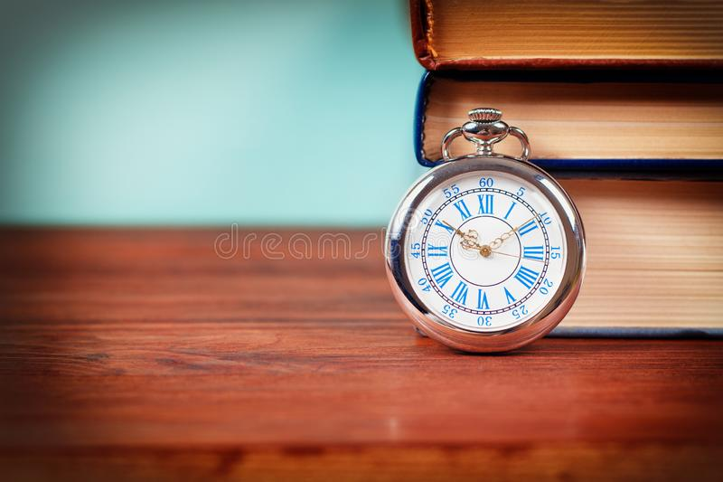 Orologio da tasca vecchio con i vecchi libri fotografia stock libera da diritti