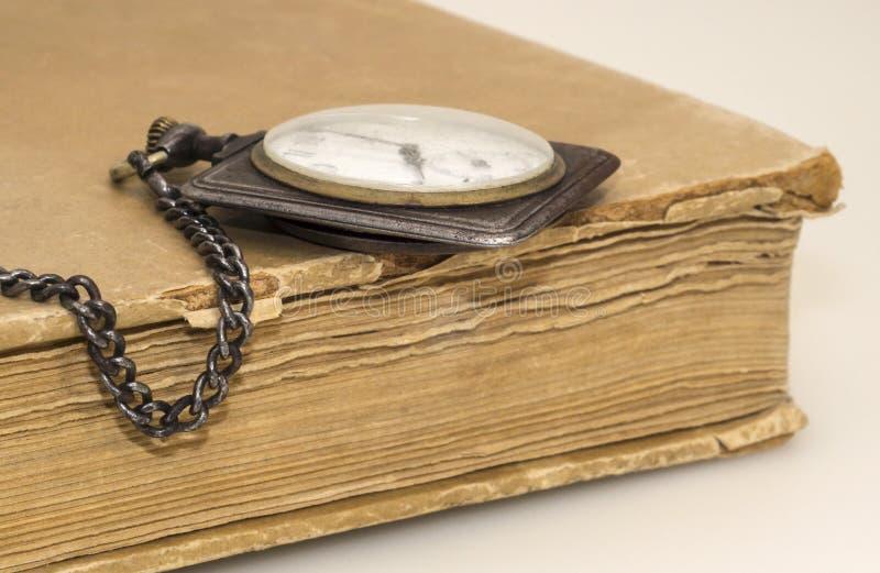 Vecchio orologio e libro stracciato fotografia stock libera da diritti
