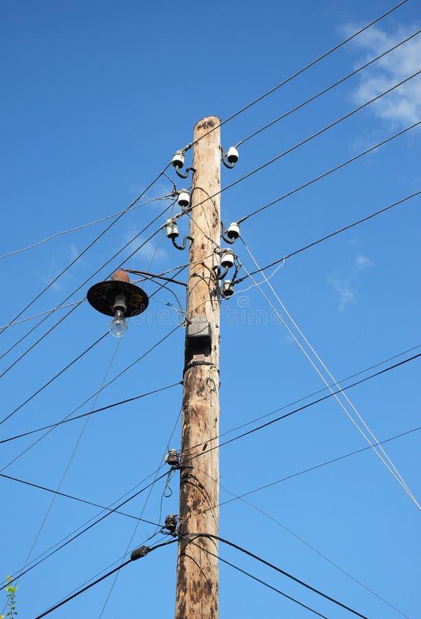 Vecchio palo di potere elettrico di legno della posta Riga di energia elettrica Palo pratico di legno con la lampadina fotografia stock libera da diritti