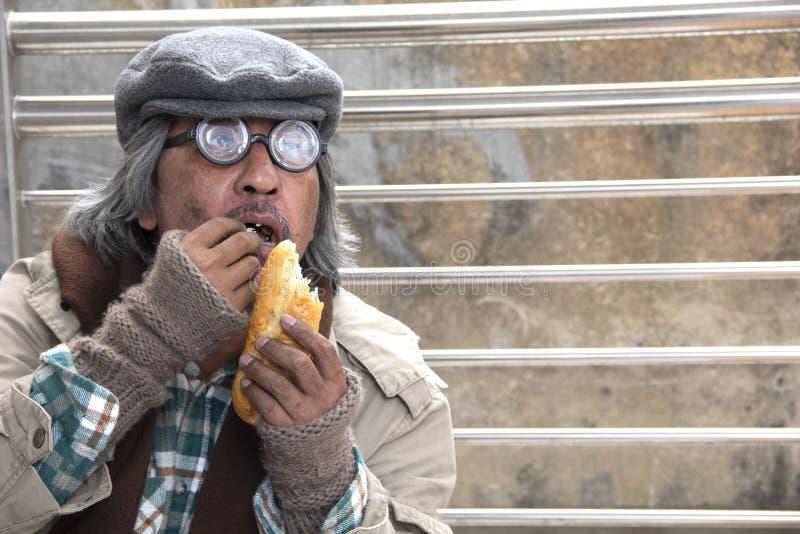 Vecchio pane mangiatore di uomini senza tetto sulla via del passaggio pedonale fotografia stock libera da diritti