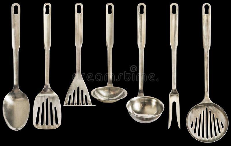 Vecchio patinato sette utensili della cucina dell'acciaio inossidabile dei pezzi messi isolati su fondo nero immagini stock