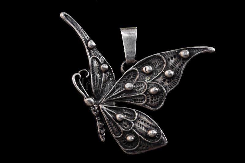 Vecchio pendente nella forma della farfalla isolato su fondo nero fotografia stock